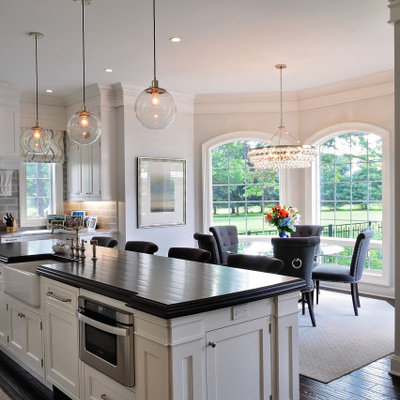 Mid-sized elegant l-shaped dark wood floor and brown floor eat-in kitchen photo in Philadelphia with a farmhouse sink, recessed-panel cabinets, white cabinets, granite countertops, gray backsplash, subway tile backsplash, paneled appliances, an island and gray countertops