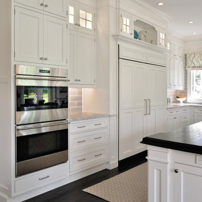 Inspiration for a mid-sized timeless l-shaped dark wood floor and brown floor eat-in kitchen remodel in Philadelphia with a farmhouse sink, recessed-panel cabinets, white cabinets, granite countertops, gray backsplash, subway tile backsplash, paneled appliances, an island and gray countertops