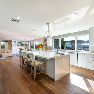 Inspiration for an expansive contemporary l-shaped open plan kitchen in Los Angeles with shaker cabinets, white cabinets, quartzite benchtops, grey splashback, glass tile splashback, stainless steel appliances, medium hardwood floors, with island, brown floor and white benchtop.