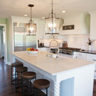 Kitchen - traditional l-shaped kitchen idea in Milwaukee with a farmhouse sink, shaker cabinets, white cabinets, white backsplash and stainless steel appliances
