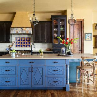 Imagen de cocina en L, de estilo americano, con fregadero bajoencimera, armarios estilo shaker, puertas de armario azules, salpicadero multicolor, electrodomésticos de acero inoxidable, suelo de madera en tonos medios, una isla, suelo marrón y encimeras beige