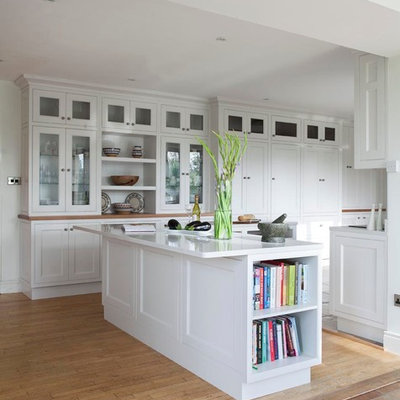 Eat-in kitchen - transitional u-shaped eat-in kitchen idea in Dublin with an undermount sink, beaded inset cabinets, white cabinets, gray backsplash, stone slab backsplash and stainless steel appliances