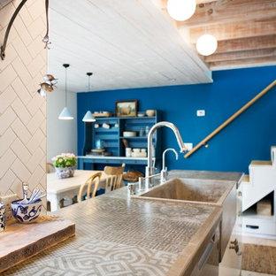サンディエゴの小さいエクレクティックスタイルのおしゃれなキッチン (エプロンフロントシンク、フラットパネル扉のキャビネット、白いキャビネット、タイルカウンター、白いキッチンパネル、セラミックタイルのキッチンパネル、シルバーの調理設備、淡色無垢フローリング、アイランドなし、ベージュの床、グレーのキッチンカウンター) の写真
