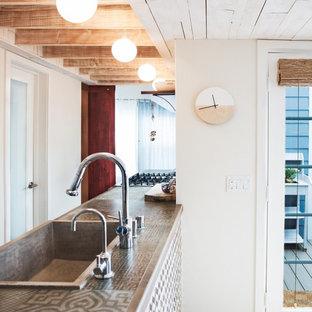 サンディエゴの小さいエクレクティックスタイルのおしゃれなキッチン (エプロンフロントシンク、フラットパネル扉のキャビネット、白いキャビネット、タイルカウンター、白いキッチンパネル、セメントタイルのキッチンパネル、シルバーの調理設備の、淡色無垢フローリング、アイランドなし、ベージュの床、グレーのキッチンカウンター) の写真