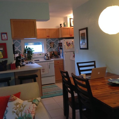 Example of a beach style l-shaped eat-in kitchen design in Miami with laminate countertops and white appliances