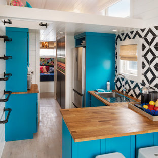 Small eclectic l-shaped open plan kitchen in Philadelphia with a drop-in sink, shaker cabinets, wood benchtops, ceramic splashback, stainless steel appliances, vinyl floors, a peninsula, timber, blue cabinets, multi-coloured splashback, beige floor and brown benchtop.
