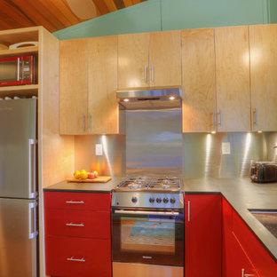 Imagen de cocina en L, moderna, pequeña, abierta, sin isla, con fregadero bajoencimera, armarios con paneles lisos, puertas de armario rojas, encimera de acrílico, salpicadero metalizado, electrodomésticos de acero inoxidable y suelo de corcho