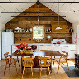 Imagen de cocina comedor lineal, campestre, con electrodomésticos blancos, armarios con paneles lisos y puertas de armario blancas