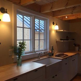 バーリントンの小さい北欧スタイルのおしゃれなキッチン (エプロンフロントシンク、フラットパネル扉のキャビネット、白いキャビネット、木材カウンター、無垢フローリング、シルバーの調理設備) の写真