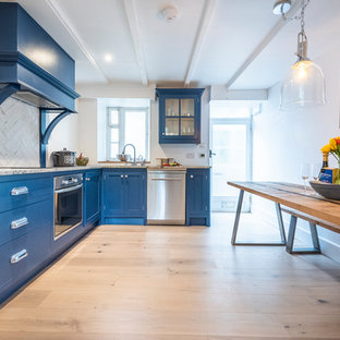 This is an example of a medium sized contemporary l-shaped kitchen in Cornwall with raised-panel cabinets, blue cabinets, granite worktops, white splashback, stainless steel appliances, medium hardwood flooring and grey worktops.
