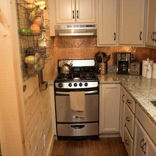 ポートランド(メイン)のシャビーシック調のおしゃれなI型キッチン (ドロップインシンク、レイズドパネル扉のキャビネット、ベージュのキャビネット、メタリックのキッチンパネル、メタルタイルのキッチンパネル、シルバーの調理設備の、竹フローリング、茶色い床) の写真