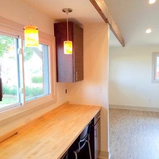 他の地域の小さいトラディショナルスタイルのおしゃれなキッチン (フラットパネル扉のキャビネット、濃色木目調キャビネット、木材カウンター、クッションフロア、アイランドなし、ドロップインシンク、シルバーの調理設備の) の写真