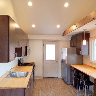 他の地域の小さいトラディショナルスタイルのおしゃれなキッチン (ドロップインシンク、フラットパネル扉のキャビネット、濃色木目調キャビネット、木材カウンター、シルバーの調理設備の、クッションフロア、アイランドなし) の写真