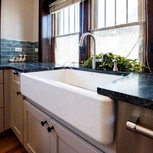 シカゴの小さいおしゃれなキッチン (エプロンフロントシンク、シェーカースタイル扉のキャビネット、グレーのキャビネット、御影石カウンター、青いキッチンパネル、ガラスタイルのキッチンパネル、シルバーの調理設備、無垢フローリング、アイランドなし、茶色い床、緑のキッチンカウンター) の写真