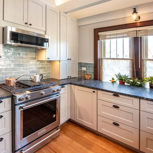 Photo of a small arts and crafts u-shaped eat-in kitchen in Chicago with a farmhouse sink, shaker cabinets, grey cabinets, granite benchtops, blue splashback, glass tile splashback, stainless steel appliances, medium hardwood floors, no island, brown floor and green benchtop.