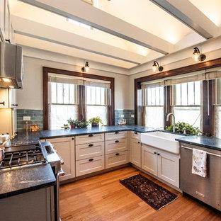 シカゴの小さいおしゃれなキッチン (エプロンフロントシンク、シェーカースタイル扉のキャビネット、グレーのキャビネット、御影石カウンター、青いキッチンパネル、ガラスタイルのキッチンパネル、シルバーの調理設備の、無垢フローリング、アイランドなし、茶色い床、緑のキッチンカウンター) の写真