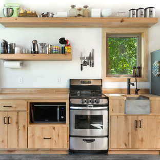 Contemporary kitchen inspiration - Trendy single-wall concrete floor and gray floor kitchen photo in Other with a farmhouse sink, flat-panel cabinets, medium tone wood cabinets, wood countertops, brown backsplash, wood backsplash, stainless steel appliances and brown countertops