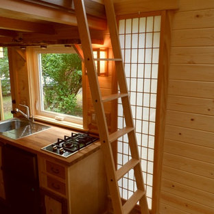 Asiatisk inredning av ett kök, med en nedsänkt diskho, träbänkskiva, släta luckor, rostfria vitvaror och mörkt trägolv