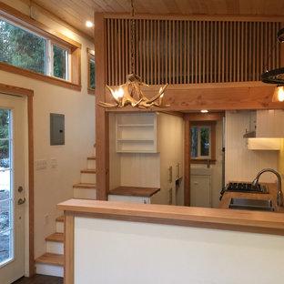 バンクーバーの小さいラスティックスタイルのおしゃれなキッチン (ダブルシンク、フラットパネル扉のキャビネット、白いキャビネット、木材カウンター、黄色いキッチンパネル、シルバーの調理設備の、クッションフロア) の写真