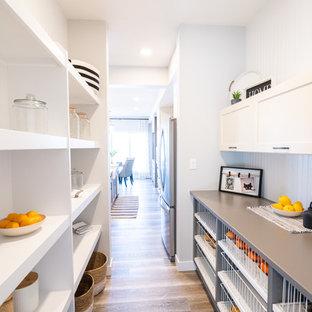 エドモントンの中くらいのトランジショナルスタイルのおしゃれなキッチン (シェーカースタイル扉のキャビネット、白いキャビネット、クオーツストーンカウンター、白いキッチンパネル、木材のキッチンパネル、無垢フローリング、アイランドなし、茶色い床、グレーのキッチンカウンター) の写真