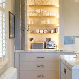 ウィルトシャーのトランジショナルスタイルのおしゃれなアイランドキッチン (フラットパネル扉のキャビネット、グレーのキャビネット、大理石カウンター、淡色無垢フローリング) の写真