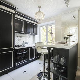 Imagen de cocina de galera, tradicional, abierta, con armarios con paneles con relieve, puertas de armario negras, salpicadero blanco, salpicadero de azulejos tipo metro, electrodomésticos negros y península