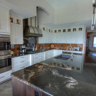 バンクーバーの広いエクレクティックスタイルのおしゃれなキッチン (アンダーカウンターシンク、シェーカースタイル扉のキャビネット、ベージュのキャビネット、御影石カウンター、黄色いキッチンパネル、ガラスタイルのキッチンパネル、シルバーの調理設備、セラミックタイルの床) の写真