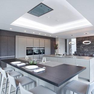 Offene, Große, Zweizeilige Moderne Küche mit flächenbündigen Schrankfronten, beigen Schränken, Quarzwerkstein-Arbeitsplatte, Küchengeräten aus Edelstahl, Keramikboden, zwei Kücheninseln, beigem Boden und Unterbauwaschbecken in Sonstige