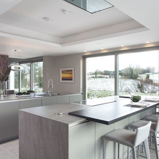 Large modern single-wall open plan kitchen in Belfast with a drop-in sink, flat-panel cabinets, beige cabinets, quartz benchtops, stainless steel appliances, ceramic floors, multiple islands and beige floor.
