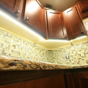 Mid-sized contemporary l-shaped eat-in kitchen in Jacksonville with a farmhouse sink, shaker cabinets, brown cabinets, granite benchtops, beige splashback, glass tile splashback, stainless steel appliances, porcelain floors and no island.