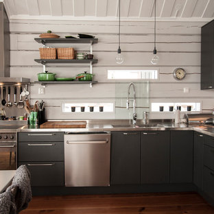 Inspiration for a medium sized urban l-shaped kitchen/diner in Gothenburg with a double-bowl sink, flat-panel cabinets, black cabinets, stainless steel worktops, stainless steel appliances and medium hardwood flooring.