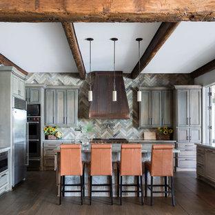 Diseño de cocina en U, rural, con fregadero sobremueble, armarios estilo shaker, puertas de armario con efecto envejecido, salpicadero multicolor, electrodomésticos de acero inoxidable, suelo de madera oscura, una isla y suelo marrón