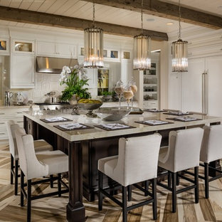 Classic kitchen in Philadelphia with shaker cabinets, beige cabinets, beige splashback, stainless steel appliances and an island.