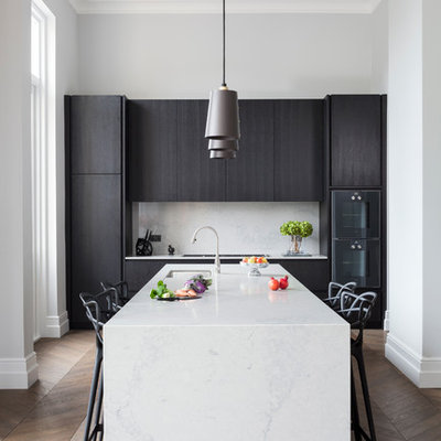 Mid-sized trendy single-wall medium tone wood floor and brown floor eat-in kitchen photo in London with flat-panel cabinets, dark wood cabinets, black appliances, an integrated sink, solid surface countertops, stone slab backsplash and a peninsula