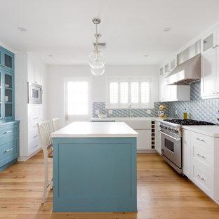Geschlossene, Mittelgroße Klassische Küche in L-Form mit Landhausspüle, Schrankfronten im Shaker-Stil, blauen Schränken, Küchenrückwand in Blau, hellem Holzboden, Kücheninsel und orangem Boden in Los Angeles