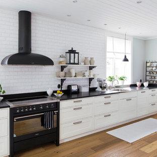 Стильный дизайн: большая кухня в скандинавском стиле с одинарной раковиной, фасадами в стиле шейкер, белыми фасадами, черной техникой, паркетным полом среднего тона и островом - последний тренд