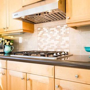 ロサンゼルスの中くらいのビーチスタイルのおしゃれなキッチン (アンダーカウンターシンク、落し込みパネル扉のキャビネット、中間色木目調キャビネット、クオーツストーンカウンター、ベージュキッチンパネル、磁器タイルのキッチンパネル、シルバーの調理設備、トラバーチンの床、ベージュの床、グレーのキッチンカウンター) の写真