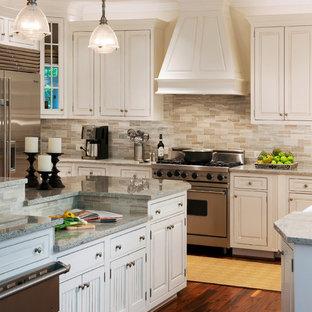 Exemple d'une cuisine chic avec un électroménager en acier inoxydable, un placard à porte affleurante, des portes de placard blanches, un plan de travail en granite, une crédence grise et une crédence en travertin.