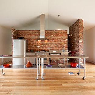 Modelo de cocina lineal, industrial, abierta, con armarios abiertos, puertas de armario en acero inoxidable, encimera de acero inoxidable, electrodomésticos de acero inoxidable, una isla y suelo de madera en tonos medios