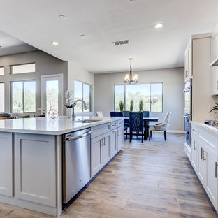 Mid-sized southwestern open concept kitchen ideas - Example of a mid-sized southwest l-shaped light wood floor and brown floor open concept kitchen design in Phoenix with an undermount sink, shaker cabinets, white cabinets, limestone countertops, multicolored backsplash, mosaic tile backsplash, stainless steel appliances and an island