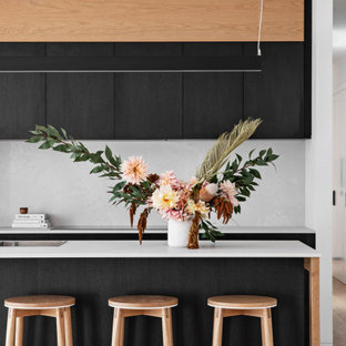 Inspiration for a modern galley kitchen in Wollongong with a drop-in sink, flat-panel cabinets, black cabinets, white splashback, stone slab splashback, stainless steel appliances, medium hardwood floors, with island, brown floor and white benchtop.