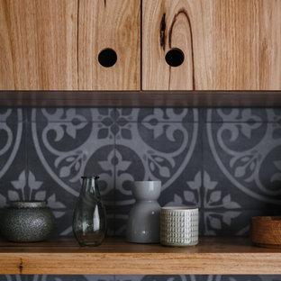 Inspiration pour une grande cuisine ouverte minimaliste en U avec un placard à porte plane, des portes de placard en bois brun, un plan de travail en surface solide, une crédence grise, une crédence en carreau de céramique, un électroménager en acier inoxydable, un sol en ardoise, un îlot central et un sol multicolore.