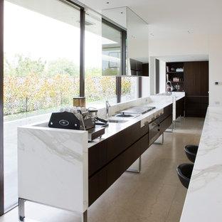 Diseño de cocina de galera, minimalista, con fregadero bajoencimera, armarios con paneles lisos, puertas de armario de madera en tonos medios, península, electrodomésticos de acero inoxidable y encimera de mármol