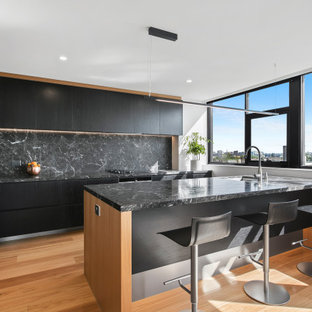 This is an example of a contemporary l-shaped kitchen in Melbourne with an undermount sink, flat-panel cabinets, black cabinets, black splashback, stainless steel appliances, medium hardwood floors, a peninsula, brown floor and black benchtop.