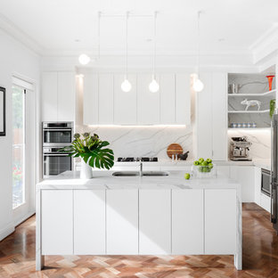 This is an example of a contemporary l-shaped kitchen in Melbourne with an undermount sink, flat-panel cabinets, white cabinets, grey splashback, stainless steel appliances, medium hardwood floors, with island, brown floor and grey benchtop.