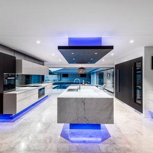 Design ideas for an expansive contemporary galley open plan kitchen in Brisbane with an undermount sink, glass-front cabinets, beige cabinets, marble benchtops, black splashback, mirror splashback, black appliances, travertine floors, with island and beige floor.