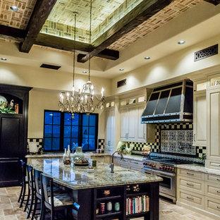 フェニックスの巨大なシャビーシック調のおしゃれなキッチン (エプロンフロントシンク、レイズドパネル扉のキャビネット、黒いキャビネット、珪岩カウンター、マルチカラーのキッチンパネル、磁器タイルのキッチンパネル、シルバーの調理設備、トラバーチンの床、マルチカラーの床、マルチカラーのキッチンカウンター) の写真