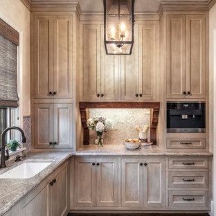 Cette image montre une grande cuisine américaine méditerranéenne en L avec un évier encastré, un placard à porte shaker, un électroménager en acier inoxydable, un sol en bois brun, aucun îlot, des portes de placard en bois vieilli, une crédence beige, une crédence en dalle de pierre, un plan de travail en granite et un sol marron.