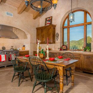 Idéer för att renovera ett stort medelhavsstil beige beige kök, med travertin golv, en undermonterad diskho, kaklad bänkskiva, beige stänkskydd, stänkskydd i terrakottakakel, rostfria vitvaror, luckor med infälld panel, skåp i mörkt trä, en köksö och beiget golv