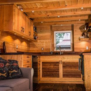 他の地域の小さいおしゃれなコの字型キッチン (ドロップインシンク、ルーバー扉のキャビネット、中間色木目調キャビネット、木材カウンター、茶色いキッチンパネル、黒い調理設備、無垢フローリング、アイランドなし、茶色い床、茶色いキッチンカウンター) の写真